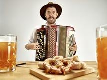 Mann in der traditionellen bayerischen Kleidung, die Akkordeon spielt oktoberfest lizenzfreie stockfotografie
