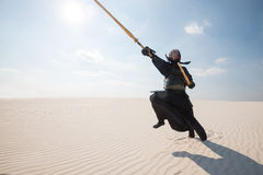 Mann in der traditionellen Rüstung für kendo, bogu in der Wüste Stockbilder