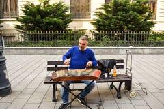 Mann, der traditionelles geh?mmertes Hackbrett mit Holzhammern spielt Straßenkünstler spielt Lieder auf den des Bukarests Straßen lizenzfreie stockfotos