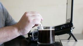 Mann, der an trinkendem Kaffee des Laptops arbeitet stock footage