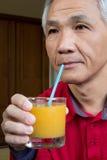 Mann der trinkender Orangensaft Stockfotografie