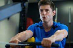 Mann in der Turnhalle trainierend auf Rudermaschine stockfotografie