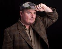 Mann in der Tweedschutzkappe auf einem schwarzen Hintergrund Lizenzfreies Stockfoto