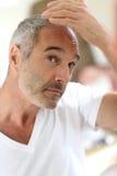 Mann, der um Haar im Badezimmer sich kümmert Lizenzfreies Stockbild