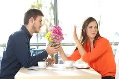 Mann, der um Verzeihen zu seiner Freundin bittet lizenzfreies stockfoto