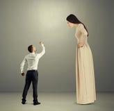 Mann, der unbefriedigter Frau Faust zeigt Stockfotos