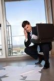 Mann, der unten verbiegt, um zerstreute Papiere zu sammeln Lizenzfreie Stockfotos