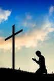 Mann, der unter dem Kreuz betet Lizenzfreie Stockbilder