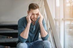 Mann, der unter Kopfschmerzen nahe Fenster leidet stockfotografie