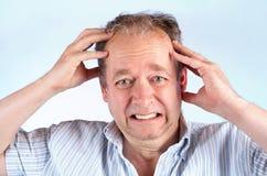 Mann, der unter Kopfschmerzen oder falschen Nachrichten leidet Lizenzfreies Stockbild