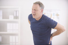 Mann, der unter Rückenschmerzen leidet Lizenzfreie Stockfotografie