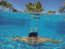 Mann, der unter Wasser in einem Swimmingpool schwimmt, Stockfoto