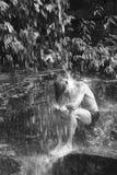 Mann, der unter Wasserfall sitzt Stockfotografie