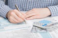 Mann, der 1040 US-Steuerformular - Atelieraufnahme ergänzt Stockfotografie