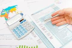 Mann, der 1040 US-Steuerformular mit silbernem Kugelschreiber - Atelieraufnahme überprüft Lizenzfreies Stockfoto