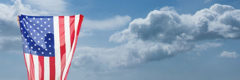 Mann, der USA-Flagge gegen Himmelhintergrund hält Stockfotografie