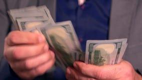 Mann, der 100 USD-Rechnungen von seiner Tasche nimmt stock video footage