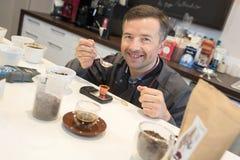 Mann, der verschiedene Arten Kaffee prüft Lizenzfreie Stockfotografie