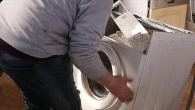 Mann, der versucht, die Waschmaschine zu reparieren stock footage