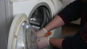 Mann, der versucht, die Waschmaschine zu reparieren stock video