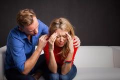 Mann, der versucht, seine Freundin unten zu beruhigen Lizenzfreies Stockfoto