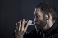 Mann, der versucht, Vorhängeschloß von den Lippen weg zu zerreißen Stockbild