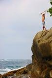 Mann, der victoriously auf einer Klippe steht Stockfotos
