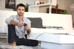 Mann, der Videospiele alleine spielt Stockfotos