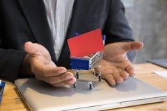 Mann, der voll eine Kreditkarte in der Minisupermarktwarenkorblaufkatze zeigt Stockfotos