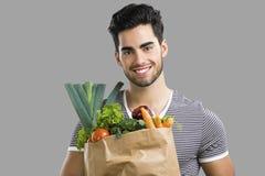 Mann, der voll eine Tasche des Gemüses trägt Stockfoto