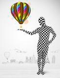 Mann in der vollen Körperklage, die Ballon hält Stockfotos