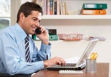 Mann, der vom Haus unter Verwendung des Laptops am Telefon arbeitet Stockfotos