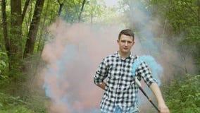 Mann, der vom Schleier des coored Rauches unter Wald auftaucht stock video