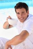 Mann, der von einer Porzellanschüssel trinkt Lizenzfreies Stockfoto
