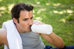Mann, der von einer Sportflasche trinkt Lizenzfreie Stockfotos