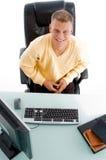 Mann, der vor Arbeitsschreibtisch sitzt Stockbilder