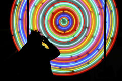 Mann, der vor Neonleuchten steht Stockbild