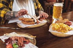 Mann, der Würste mit den Armen im Alkoholiker isst Stockbild