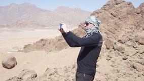 Mann in der Wüste macht Foto der Düne stock footage