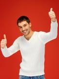 Mann in der warmen Strickjacke, die sich Daumen zeigt Lizenzfreie Stockfotos