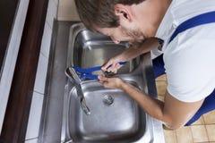 Mann, der Waschbeckenhahn repariert Stockfotografie