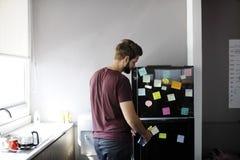 Mann, der Wasser-Flasche vom Kühlschrank im Speiseschrank-Raum während des Bruches nimmt stockfotos