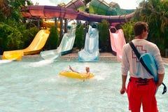 Mann, der Wasseranziehungskraft auf gelbem waterpark Rohr genießt Leibwächter, der Pool Aquatica-Gleichheit betrachtet stockfotos