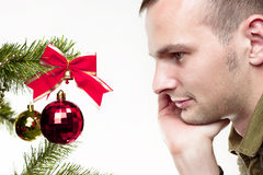Mann, der Weihnachtskugel betrachtet Lizenzfreie Stockbilder