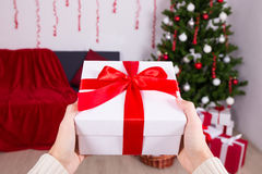 Mann, der Weihnachtspräsentkarton unter Weihnachtsbaum setzt Stockfoto