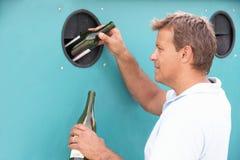 Mann an der Wiederverwertung der Mitte in Flaschen-Querneigung Stockfoto