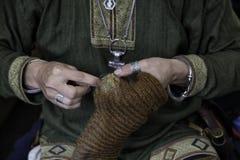 Mann, der Wollsocken ausbessert stockfotografie