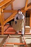 Mann, der Wärmedämmungsschicht unter das Dach legt Stockfoto