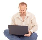 Mann, der zu Hause über dem Internet arbeitet Stockfotografie