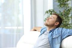 Mann, der zu Hause auf einer Couch stillsteht stockfotografie
